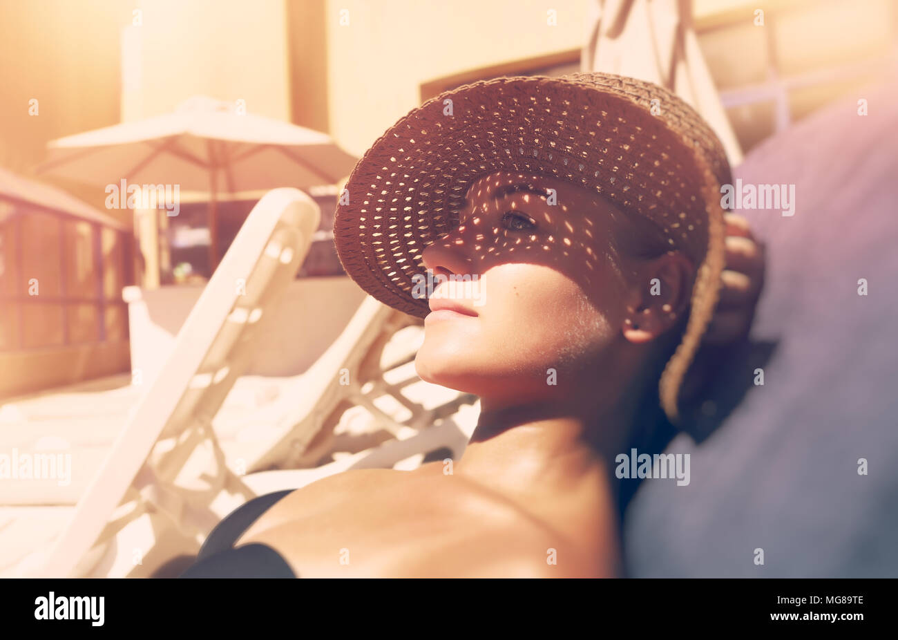 Attractive woman tanning on the beach, lying down on sunbed and taking sun, nice female hides her face from the sun under a straw hat, summer vacation - Stock Image