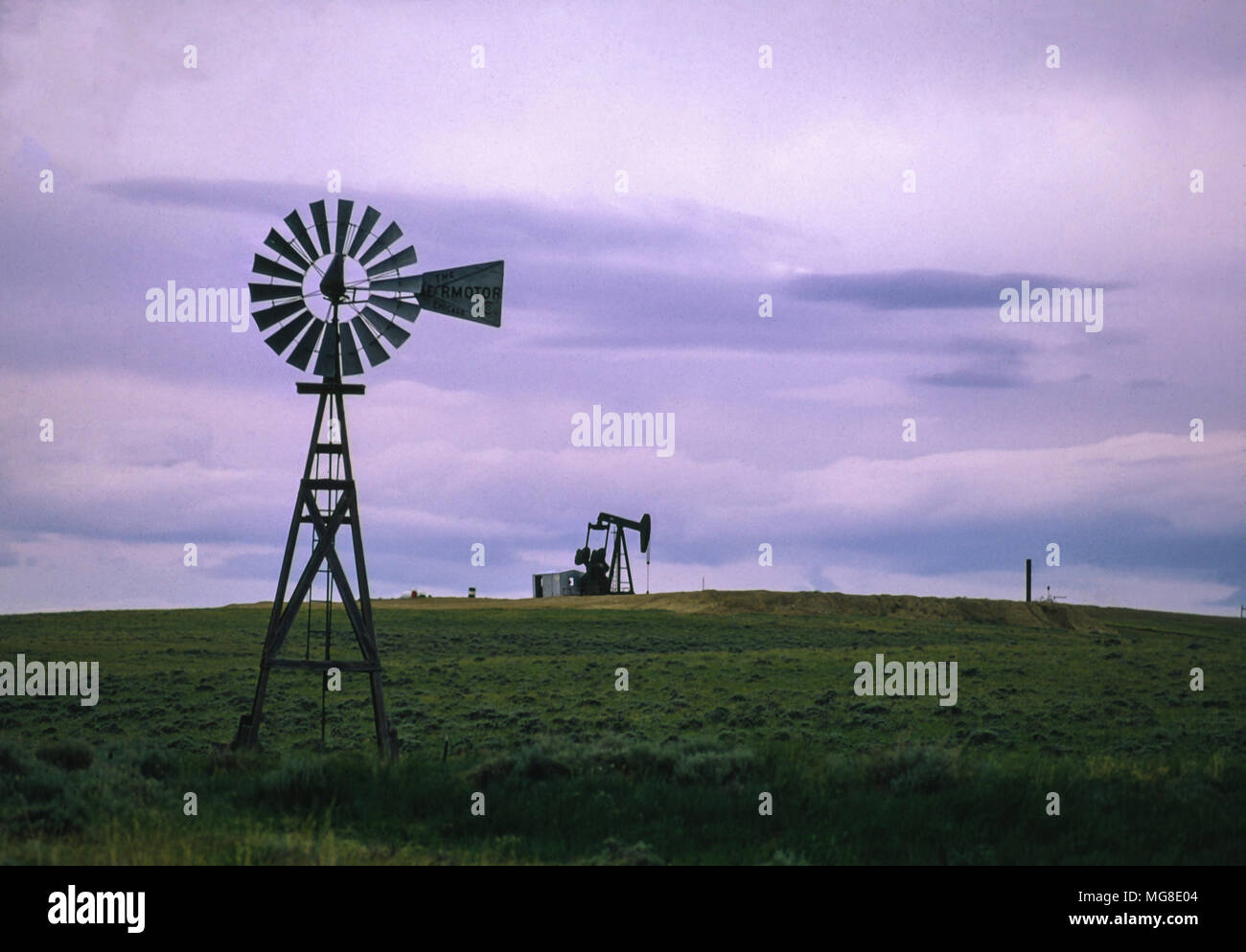 Windmill and oil well in central Wyoming, one non-polluting, the other polluting and contributing to global warming. - Stock Image