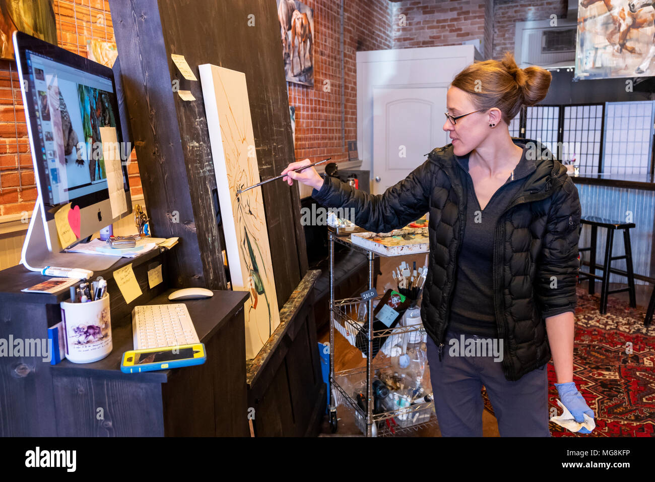 Fine artist Katie Maher referencing a computer image while creating an oil painting in her gallery; Salida; Colorado; USA - Stock Image