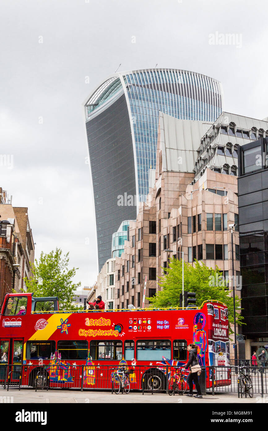 London, United Kingdom - May 2, 2015: 20 Fenchurch St, London also known the Walkie-Talkie Building with a tour bus in the foreground, on a cloudy day. - Stock Image