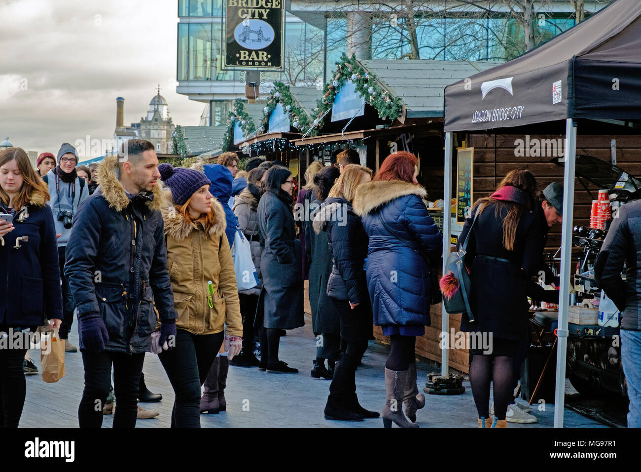 A crowd of people shop & eat at Christmas by the River Open air Christmas Market at London Bridge City, on the south bank of the River Thames, London. - Stock Image