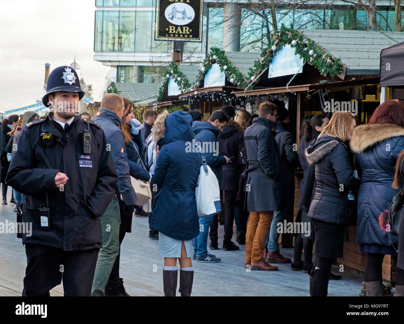 London Policeman walks by at Christmas by the River open air  Market at London Bridge City, on the south bank of the River Thames, London. - Stock Image