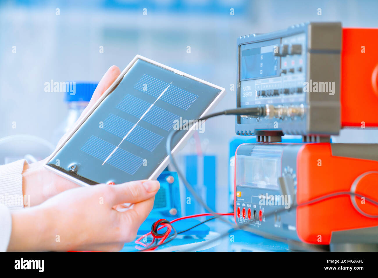 Solar battery research. Researcher holding a silicon photovoltaic element. - Stock Image