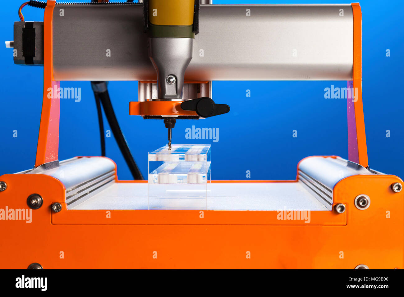 CNC milling machine drilling plastic block#. - Stock Image
