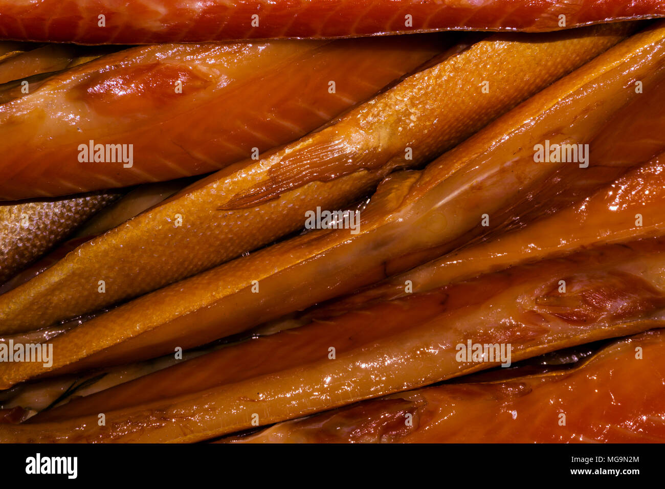 background fat golden smoked fish on the counter closeup stock