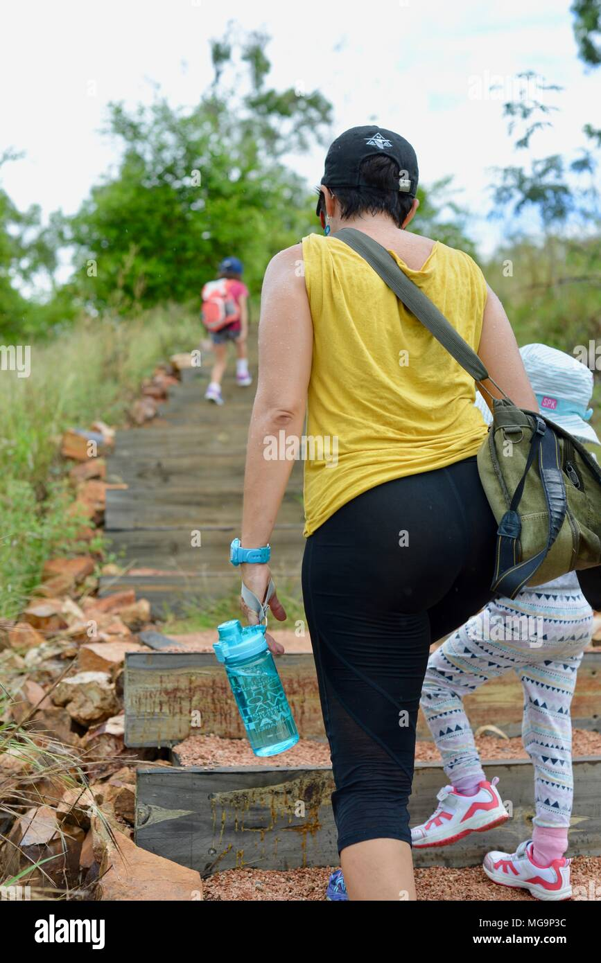 Mother and children walking on a path through open woodland, Mount Stuart hiking trails, Townsville, Queensland, Australia Stock Photo