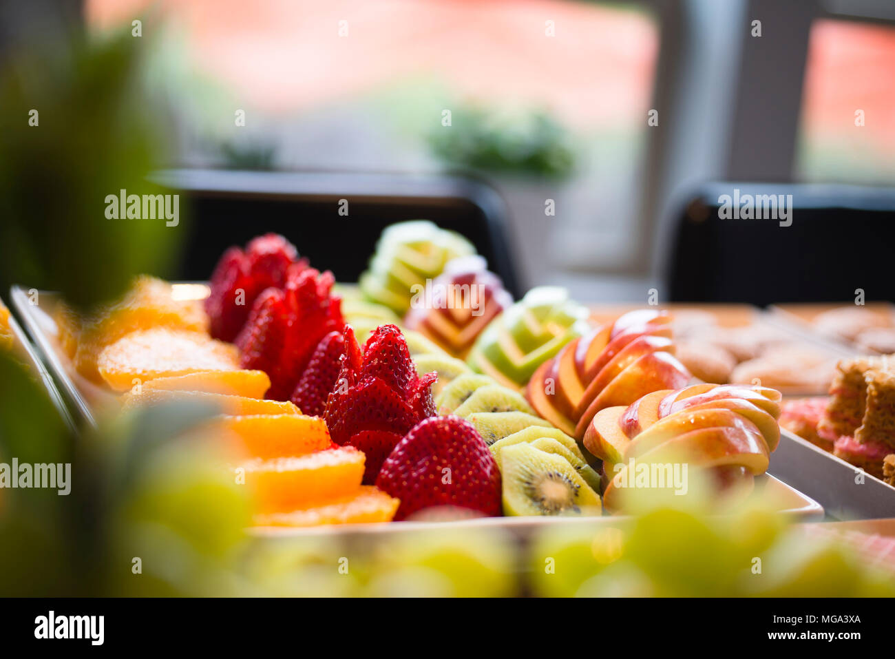 Neatly laid out delicious delicacies low-calorie desserts of sliced apples strawberry kiwi oranges and baked cookies are ready for any festive table d - Stock Image