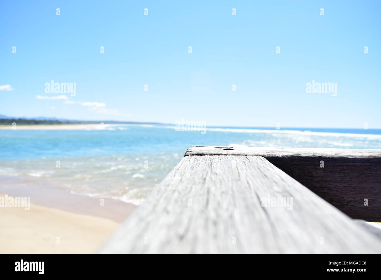 Australian beach with railing on pier on the foreground. Low depth of field, light mood. - Stock Image