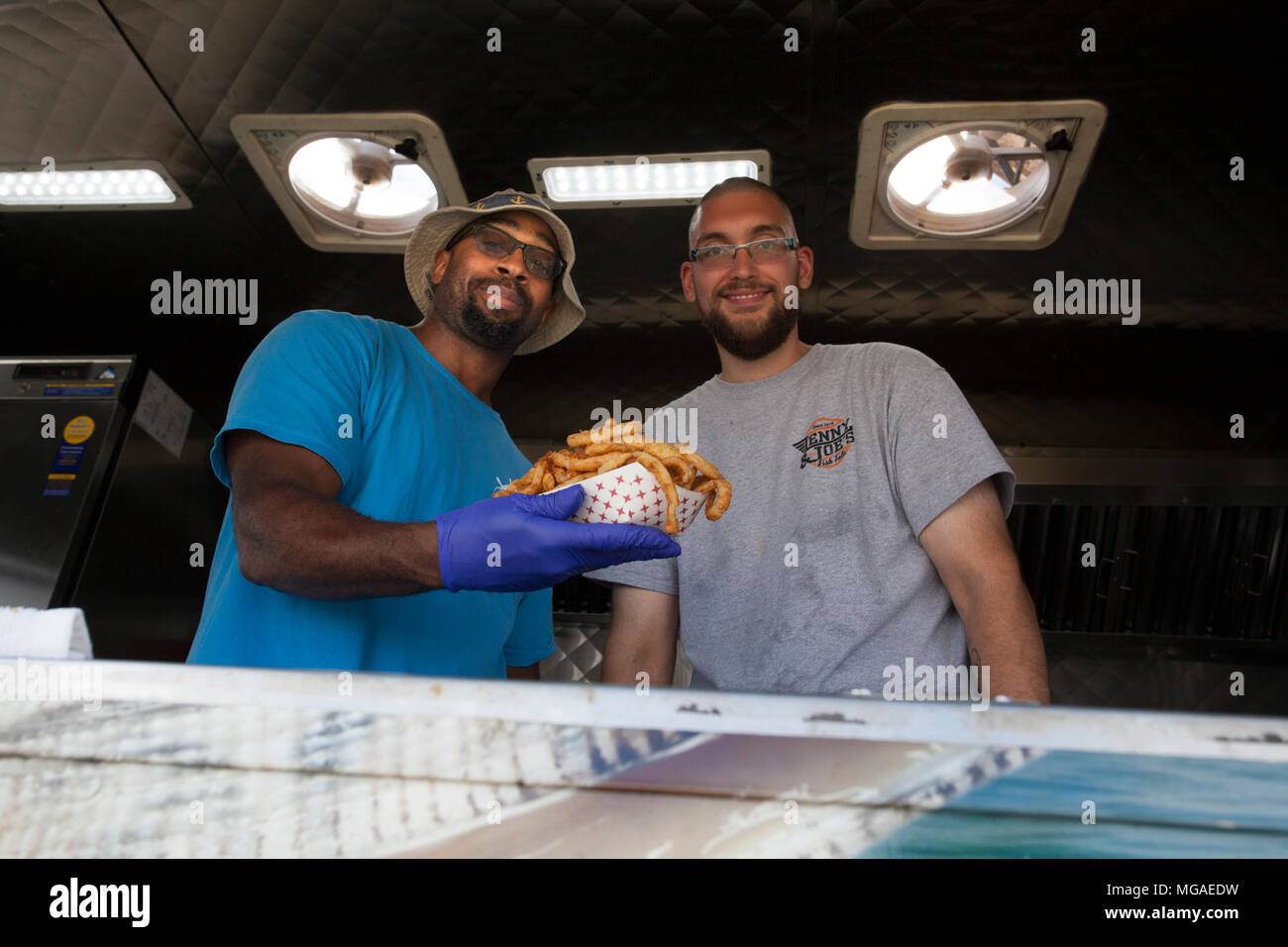 African-American and Caucasian small business owners in their food truck with a basketful of fried onion rings - Stock Image