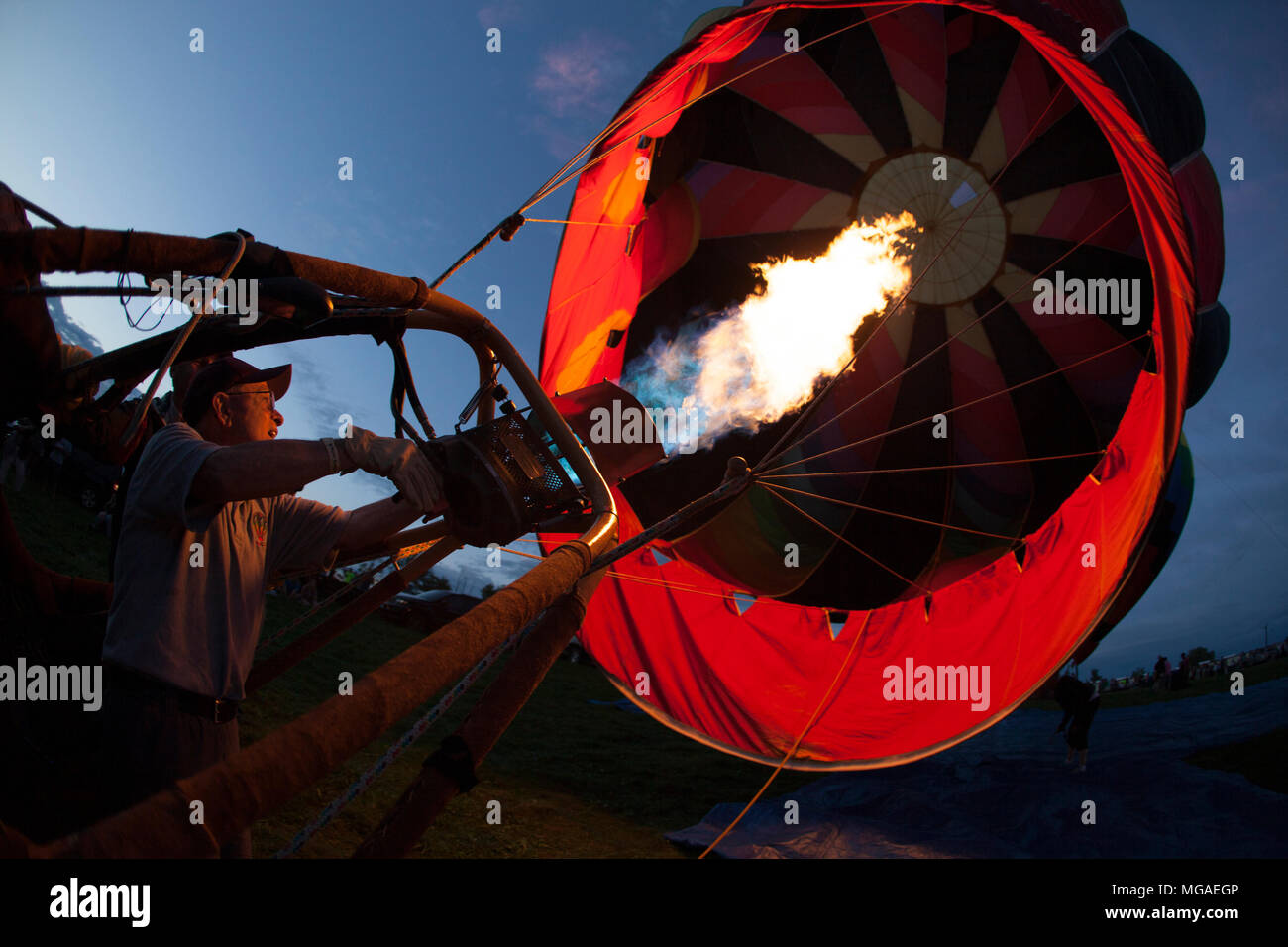 delighted hot air balloon pilot heating his balloon for an evening's glow activity heating - Stock Image