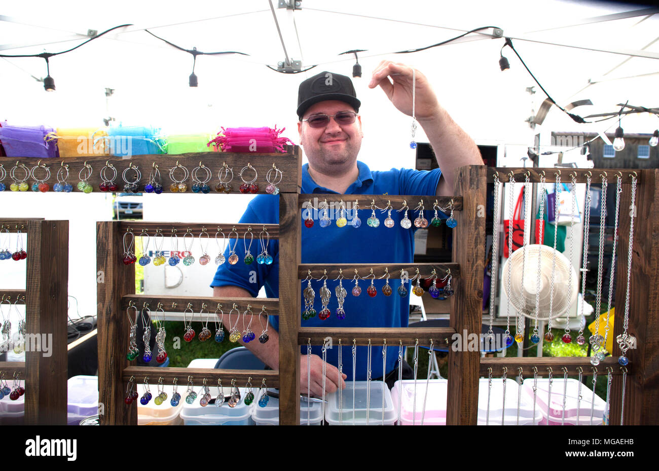 Proud small business owner displaying his handmade jewelry at a local art show - Stock Image