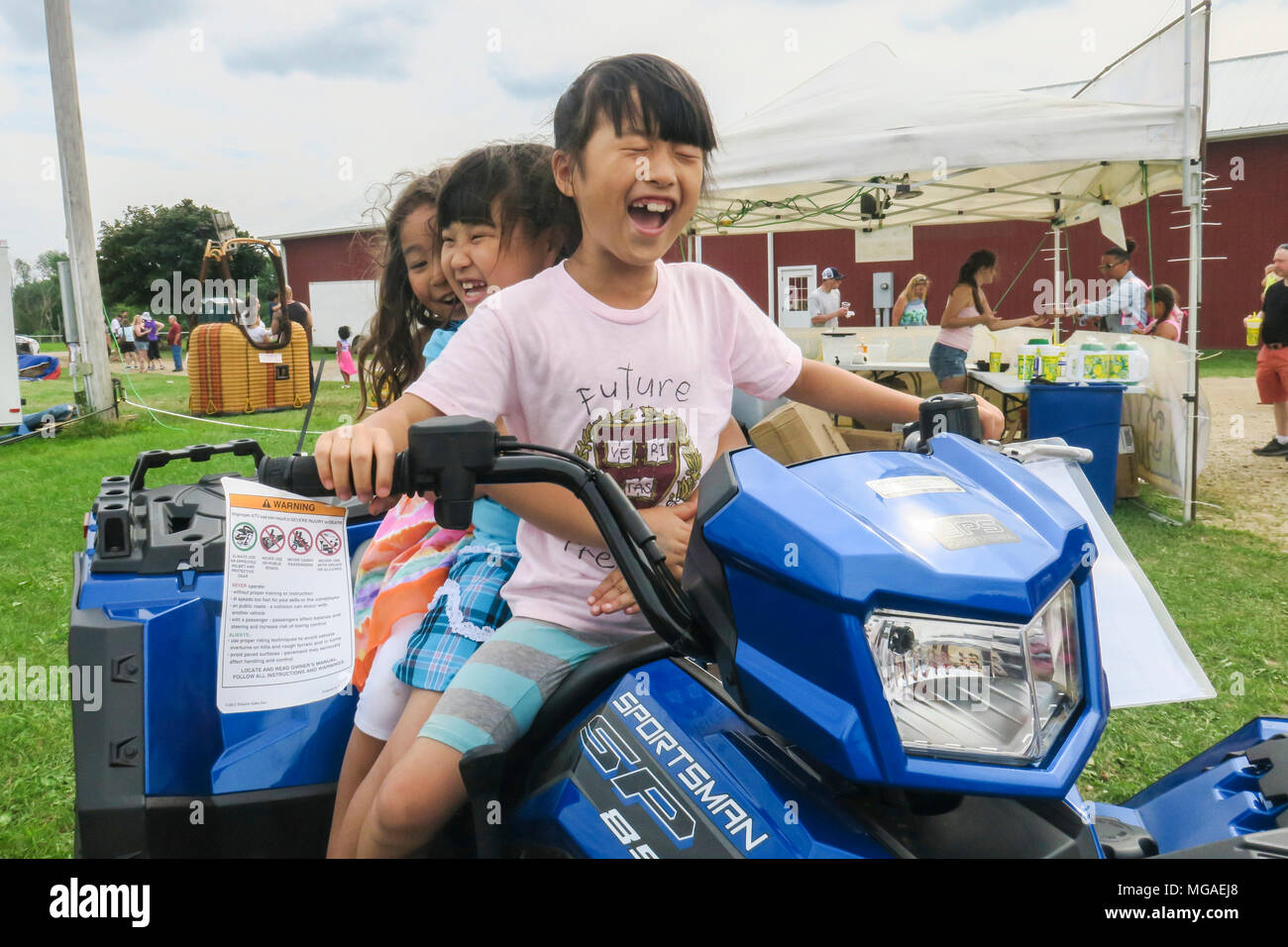 Three delighted laughing young Asian sisters sitting on a large ATV on display and a Connecticut summertime Carnival - Stock Image