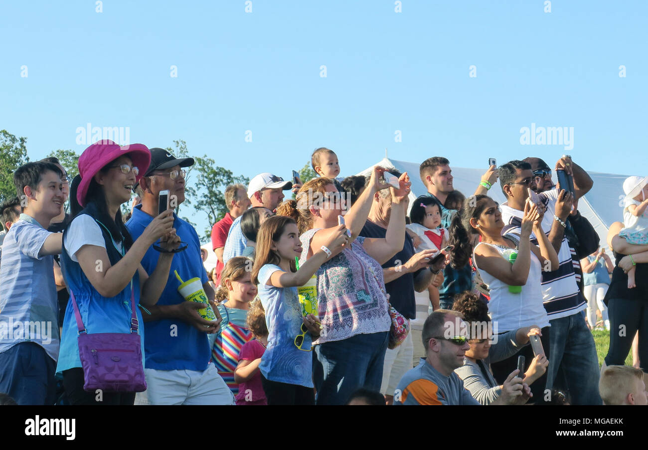 A crowd of onlookers photographing a balloon launch with a variety of handheld cameras, phones and tablets - Stock Image