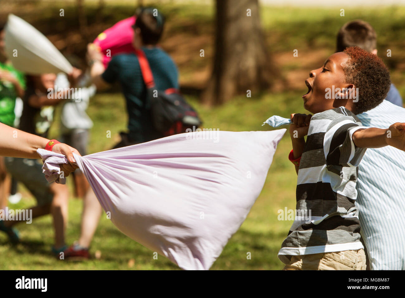 A child avoids being hit by a pillow while taking part in International Pillow Fight Day at Grant Park on April 1, 2017 in Atlanta, GA. - Stock Image