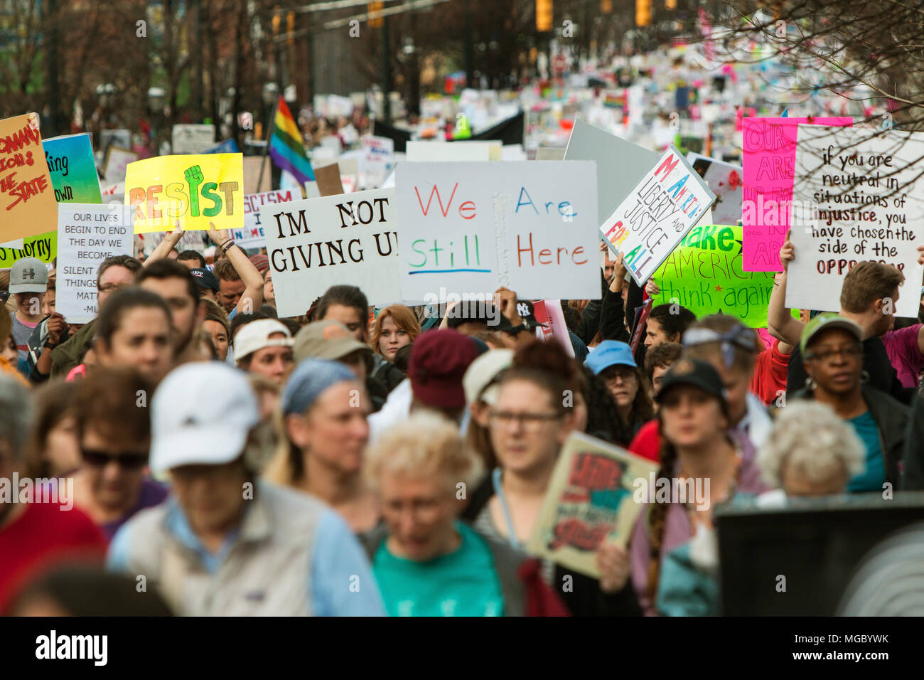 A group of protest signs rise above the crowd as thousands of protesters walk in the March For Women on January 21, 2016 in Atlanta, GA. - Stock Image