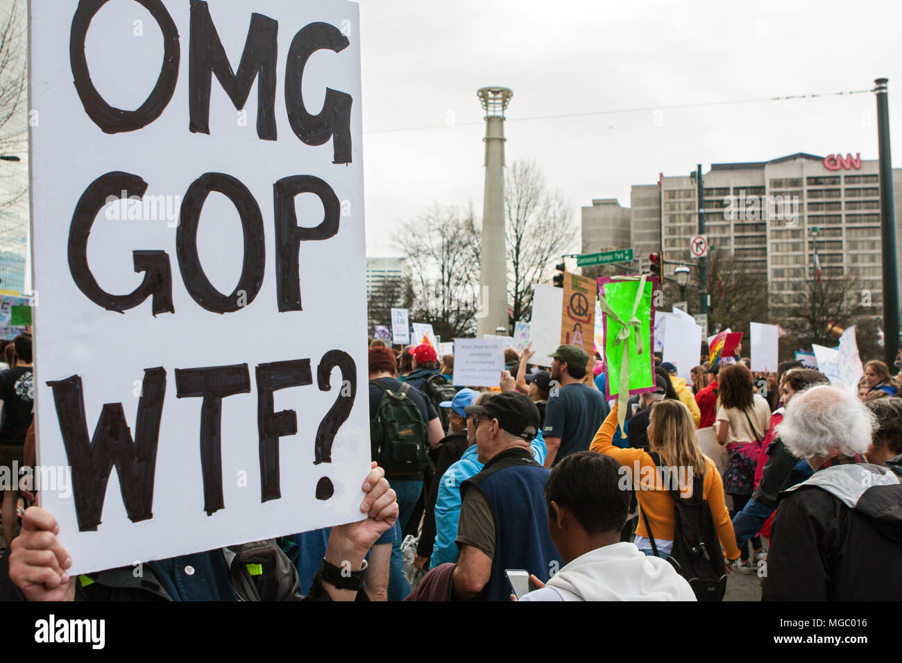 "A woman holds a sign that says ""OMG, GOP, WTF?"" as thousands of protesters pass by in the March For Women on January 21, 2016 in Atlanta, GA. Stock Photo"