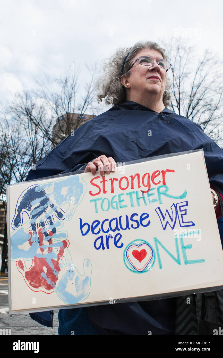 """A woman holds a sign that says """"Stronger together because we are one"""" as she participates in the March For Women on January 21, 2016 in Atlanta, GA. Stock Photo"""