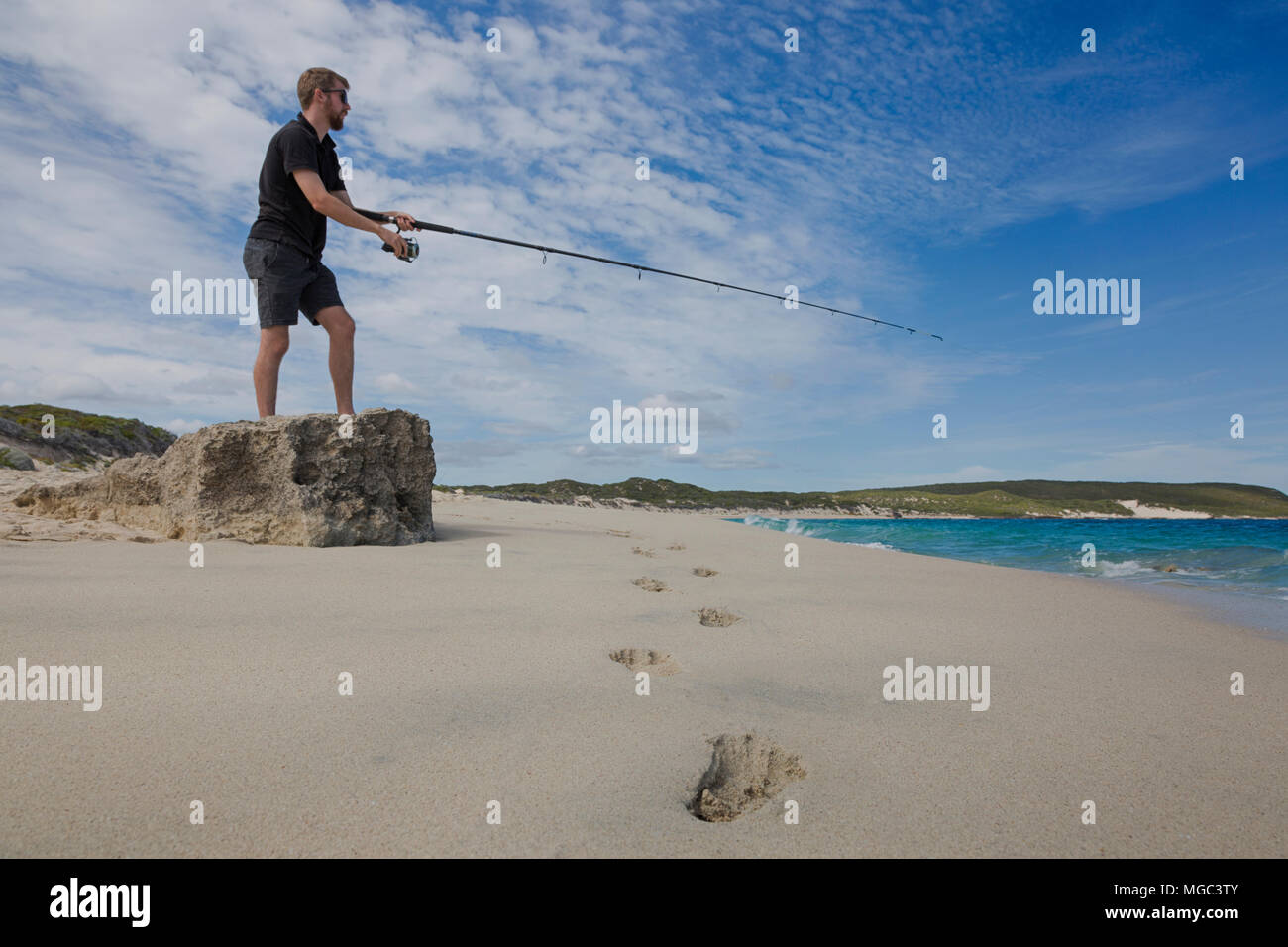 Footprints leading to a man fishing from a rock at Hamelin Bay in Australia. - Stock Image