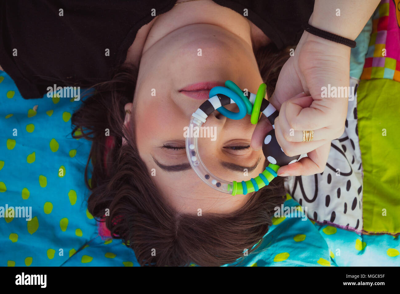 Woman lying on a colorful blanket and looking at camera through a baby toy - Stock Image