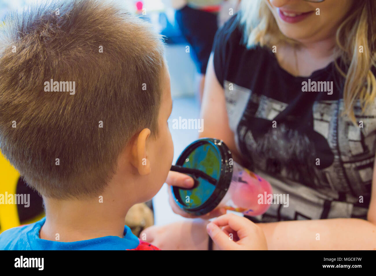 Young boy drinks sweet shaved ice at ice cream parlor Stock Photo