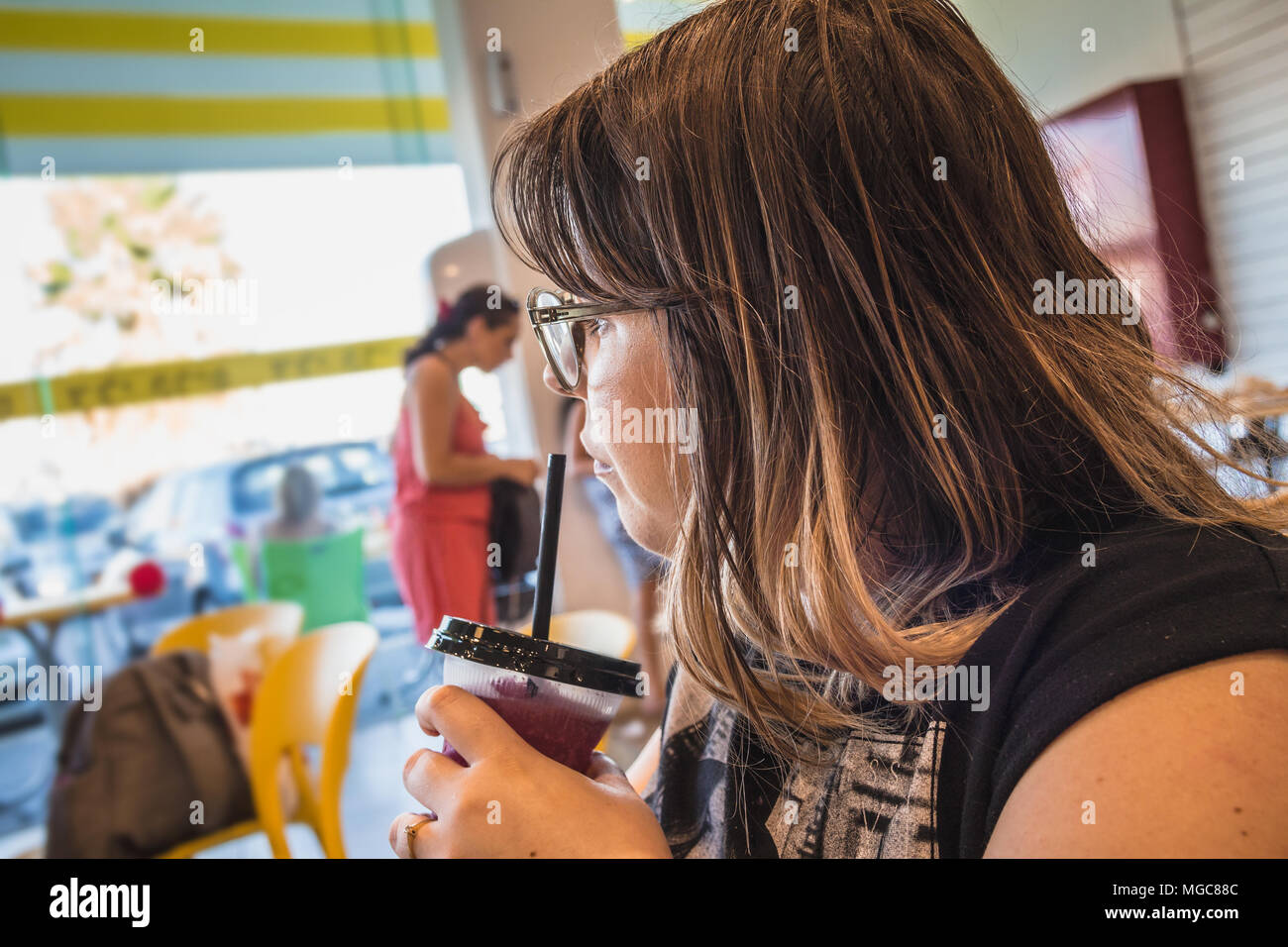 Woman drinks sweet shaved ice and looks away at ice cream parlor Stock Photo