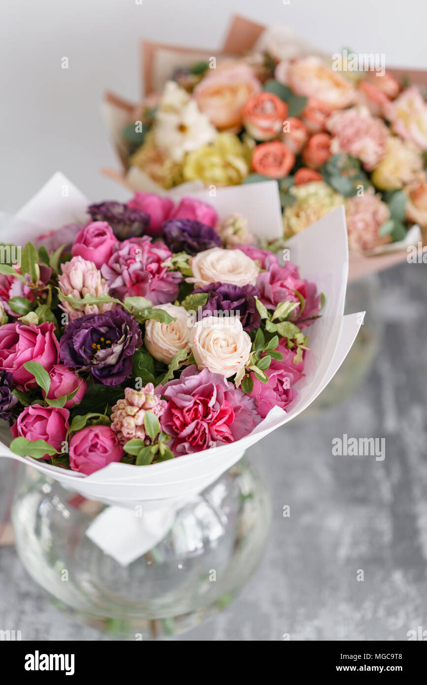 Two bouquet of beautiful flowers on gray table floristry concept two bouquet of beautiful flowers on gray table floristry concept spring colors the work of the florist at a flower shop vertical photo izmirmasajfo
