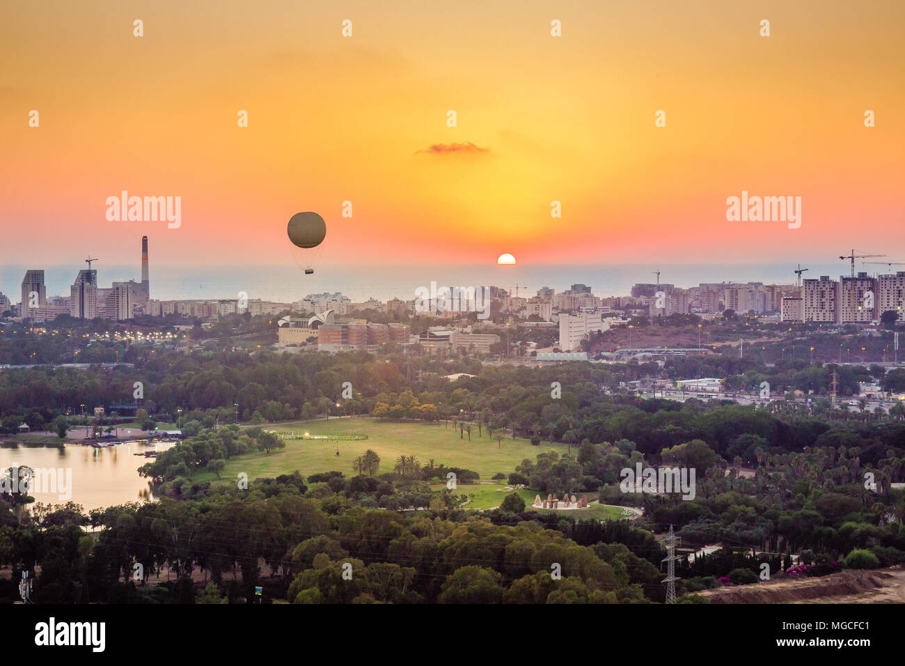 Tel Aviv skyline at sunset. Can see a hot air balloon flying in the air. In addition, can see the neighborhood in north Tel Aviv, Hayarkon Park, Readi - Stock Image