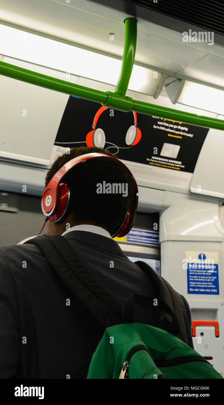 Man travelling on the London Underground, wearing red headphones, standing underneath a poster advertising red headphones, rear view - Stock Image