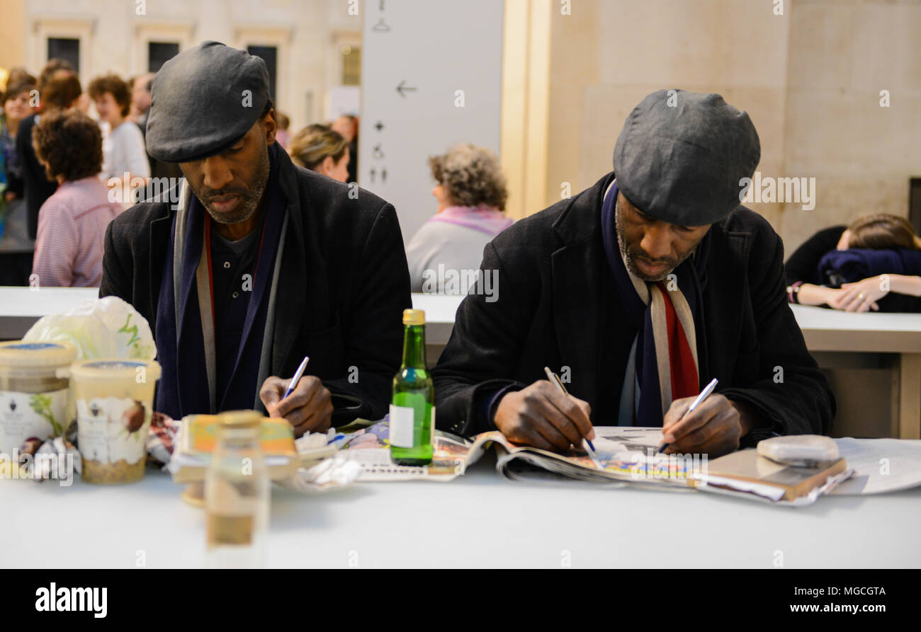 Two identical twins, sitting in cafe, wearing the same clothes, writing with both hands, simultaneously, London, England, UK - Stock Image