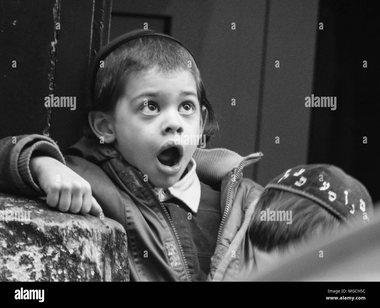 Young Jewish boy wearing kippah, looking up with shocked expression, mouth open, black and white, New York City, USA - Stock Image