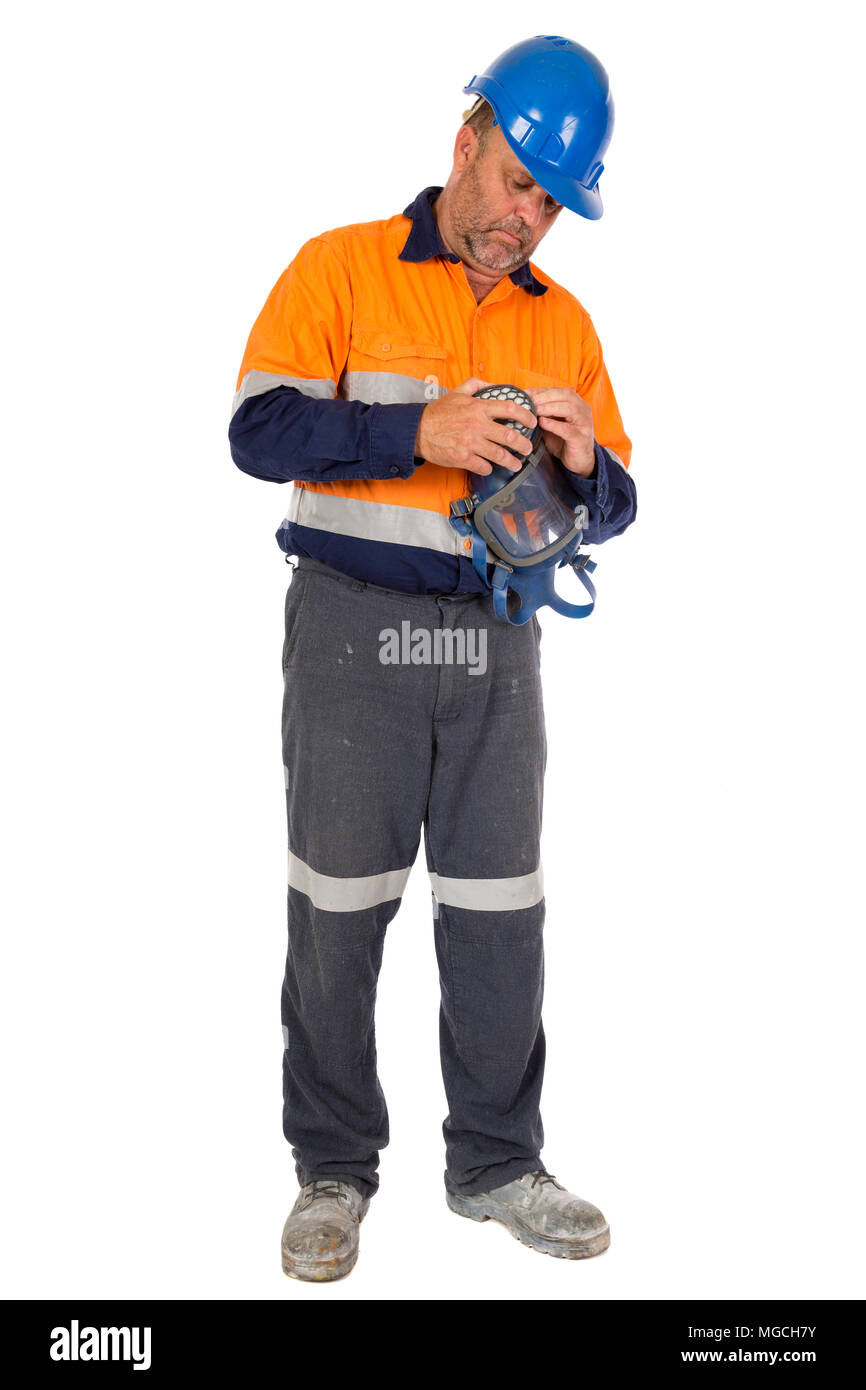 A man checking his gas mask for seal and integrity before commencing work. Safety concept. - Stock Image