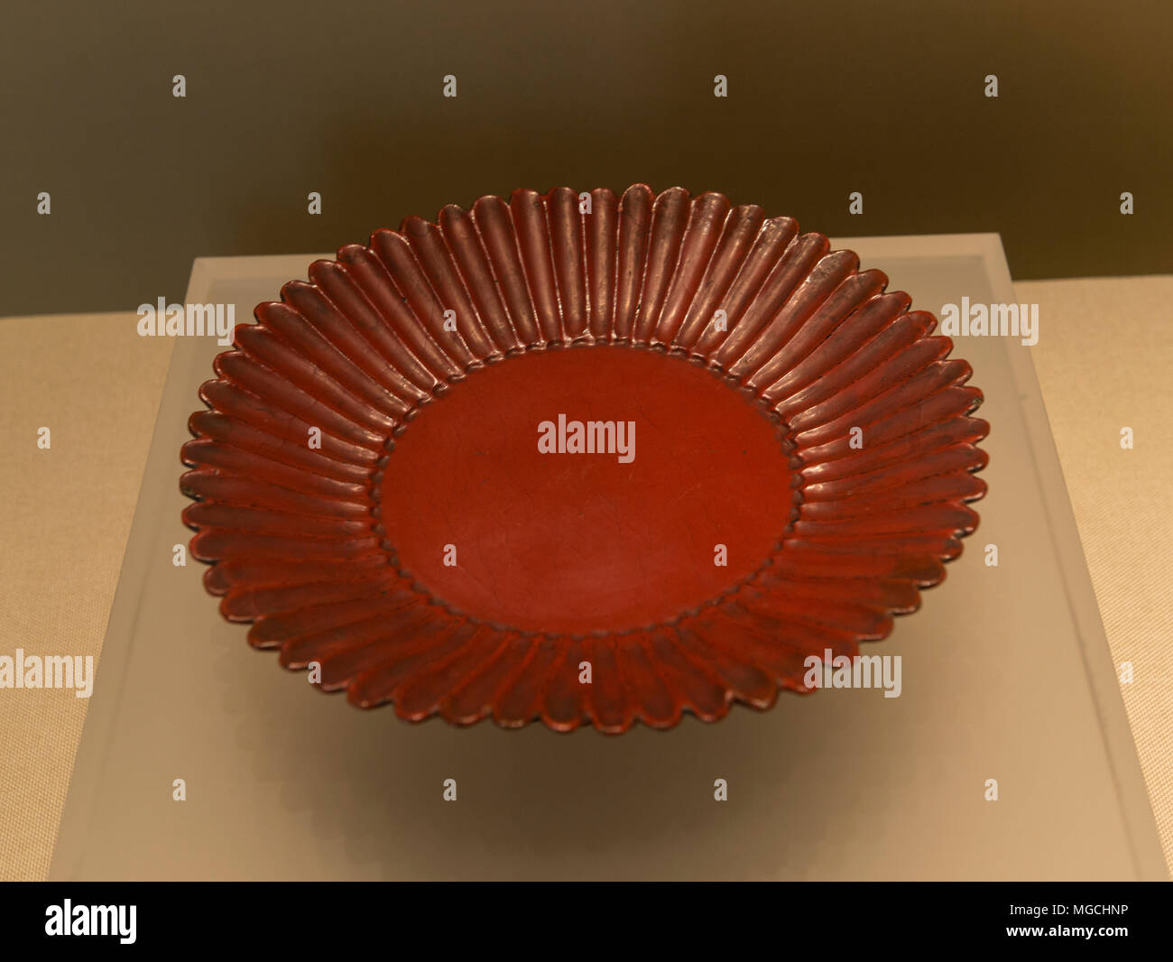 A scarlet lacquer chrysanthemum petals style plate from Yuan Dynasty(1279–1368), donated by entrepreneurial couple Cao Qiyong and Luo Bizhen to Zhejiang Museum, China. - Stock Image