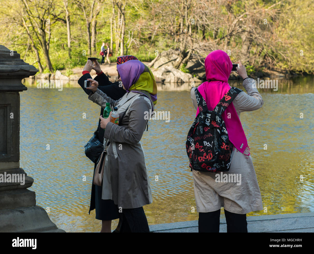 Three women, wearing colourful headscarves, taking photographs in Central Park, New York City, USA - Stock Image