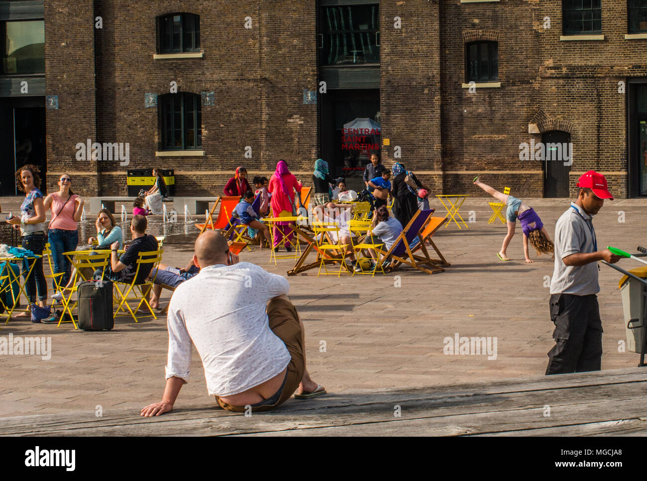 Man sitting on bench, making phone call, showing 'builders bum' rear view - Stock Image