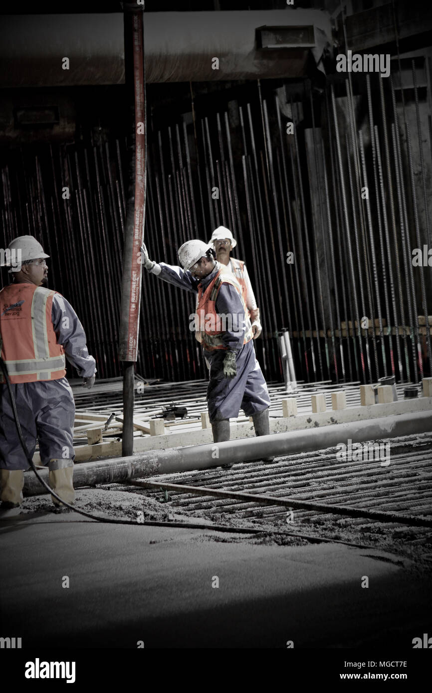 Workers pumping and placing concrete in the Montague Trench on the BART to Silicon Valley Berryessa Extension project in Milpitas, California - Stock Image