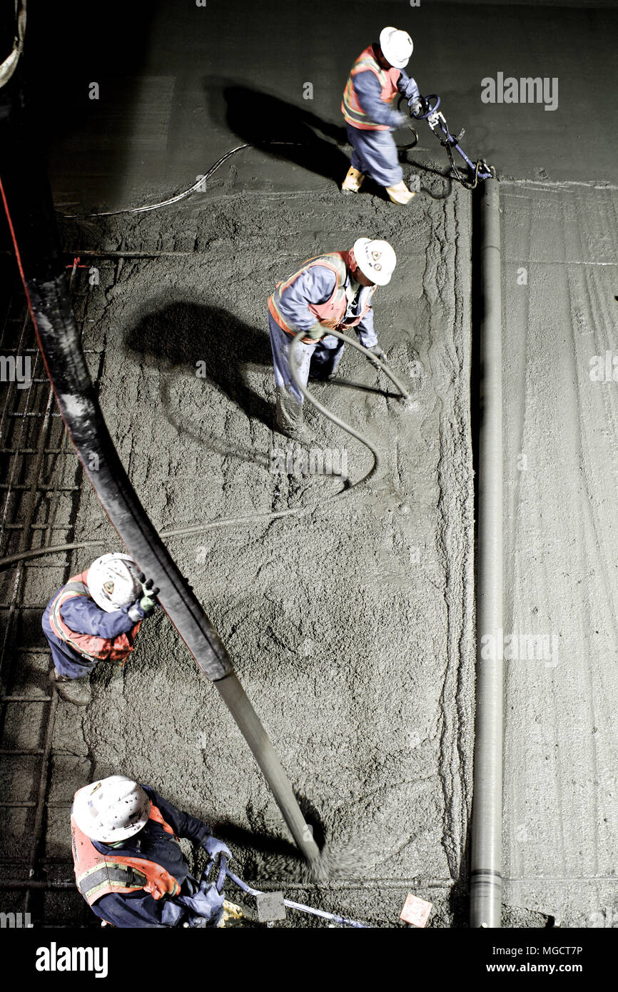 Workers screeding and finishing concrete in the Montague Trench on the BART to Silicon Valley Berryessa Extension project in Milpitas, California - Stock Image