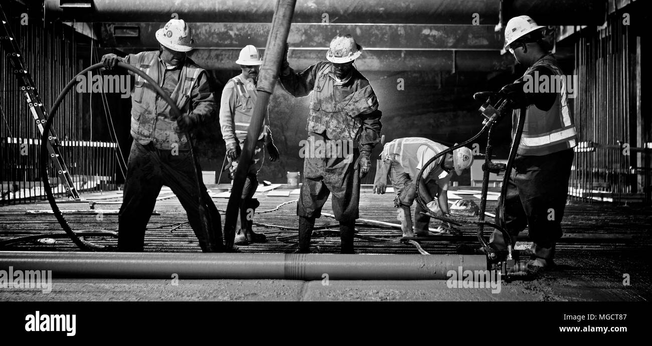 Workers placing concrete at night in the Montague Trench of the BART to Silicon Valley Berryessa Extension in Milpitas, California (Black & White) - Stock Image