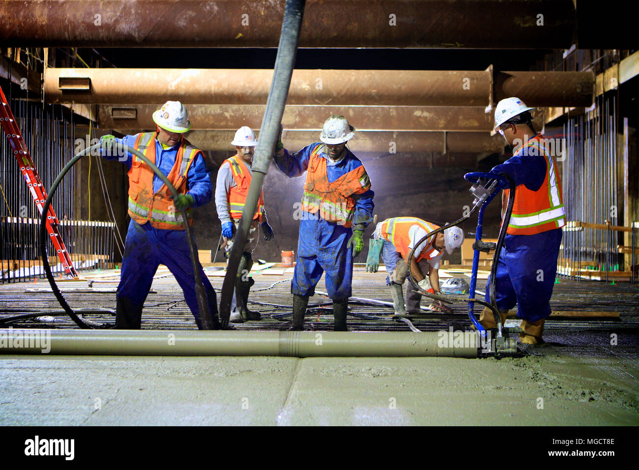 Workers placing concrete at night in the Montague Trench of the BART to Silicon Valley Berryessa Extension in Milpitas, California - Stock Image
