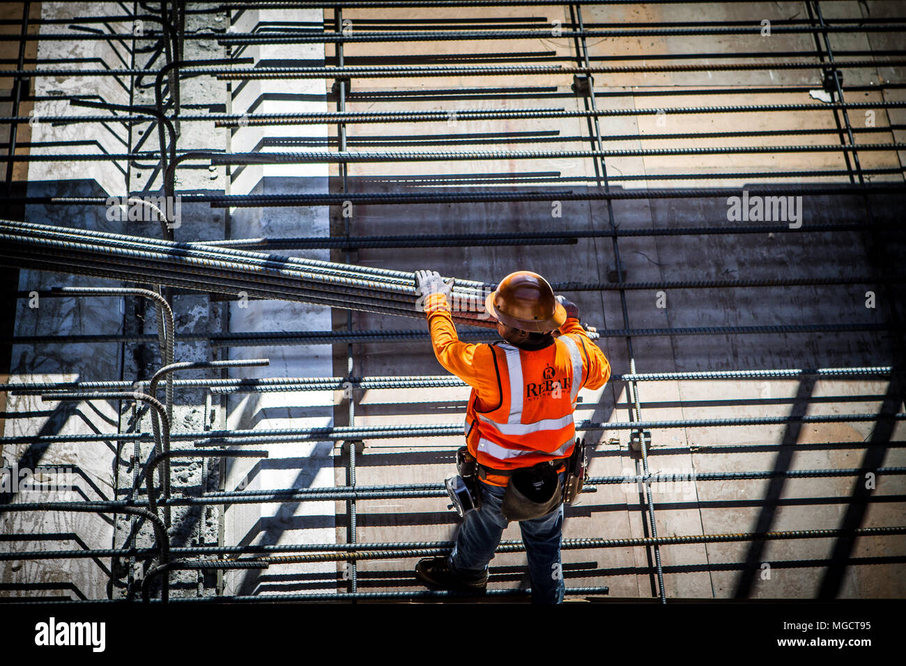 Worker lowering rebar into place in the Hostetter Trench of the BART to Silicon Valley Berryessa Extension project in San Jose, California Stock Photo