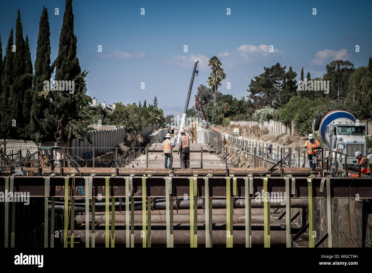 Two workers looking down the under construction Hostetter Trench on the BART to Silicon Valley Berryessa Extension project in San Jose, California - Stock Image