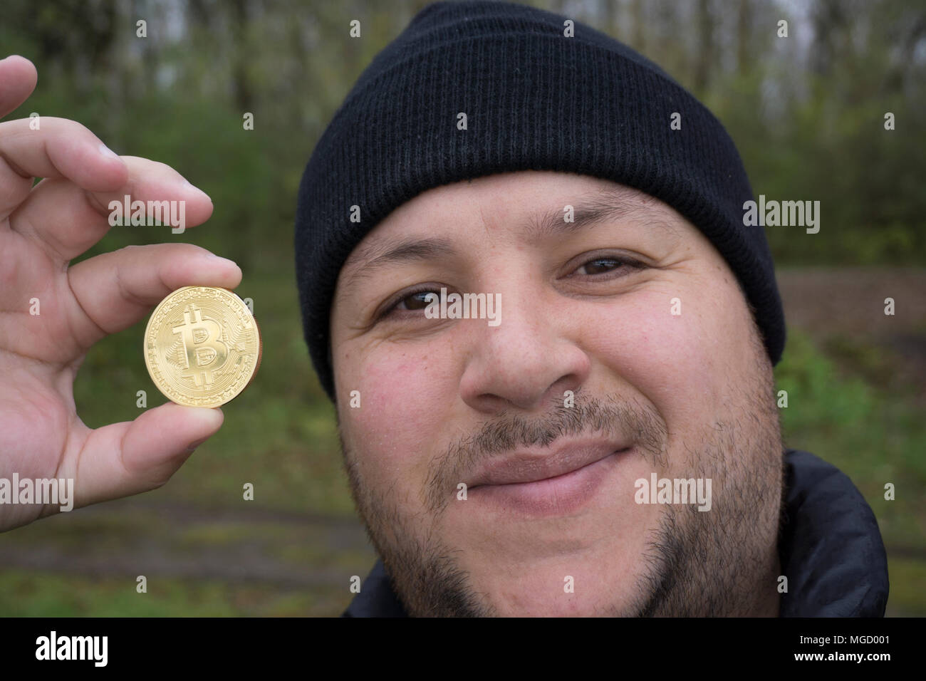 mad bitcoin lover with a gold coin in your hand , funny miner with BTC near the face - Stock Image