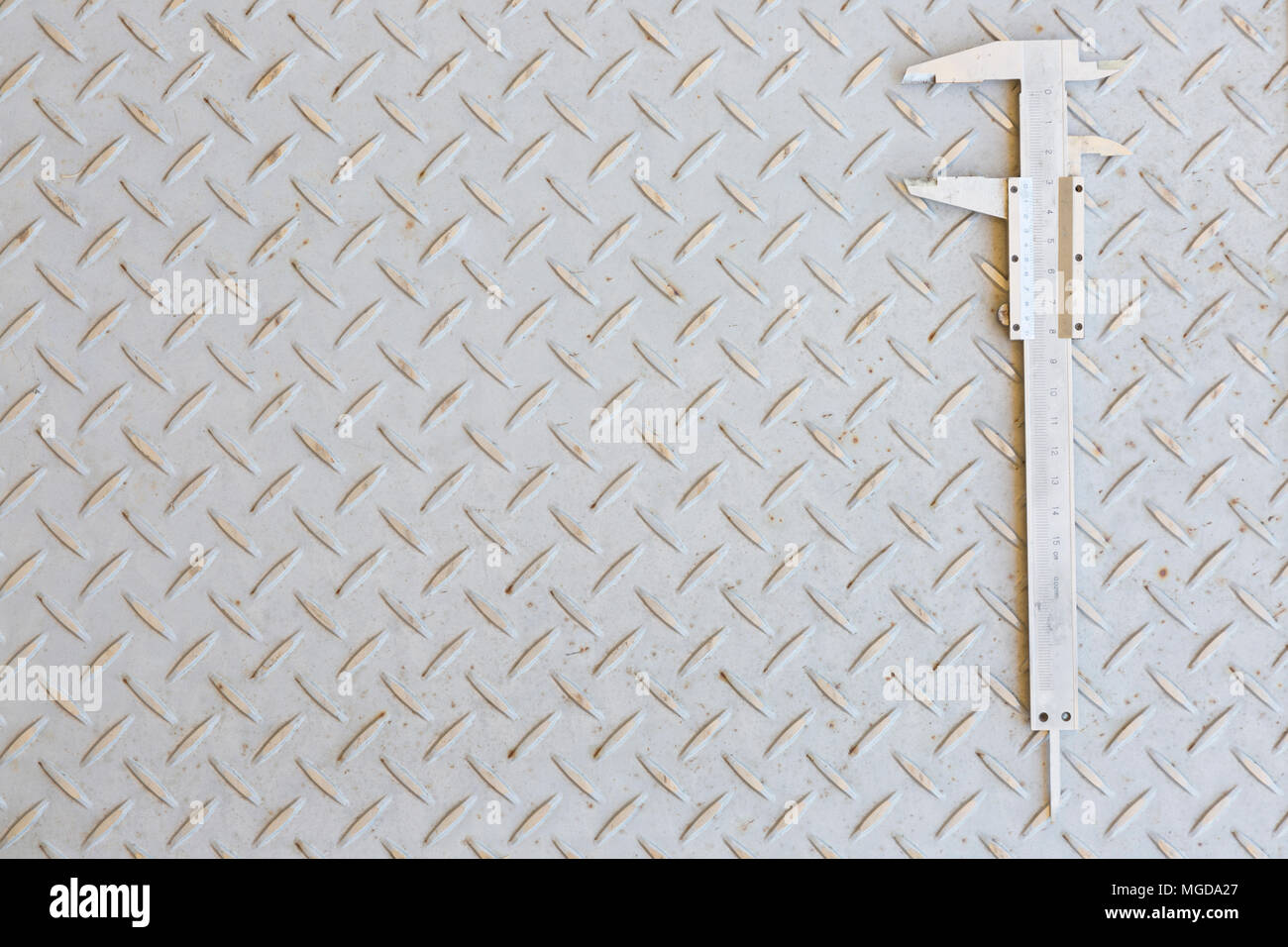 Vernier calipers on a checker plate background. - Stock Image
