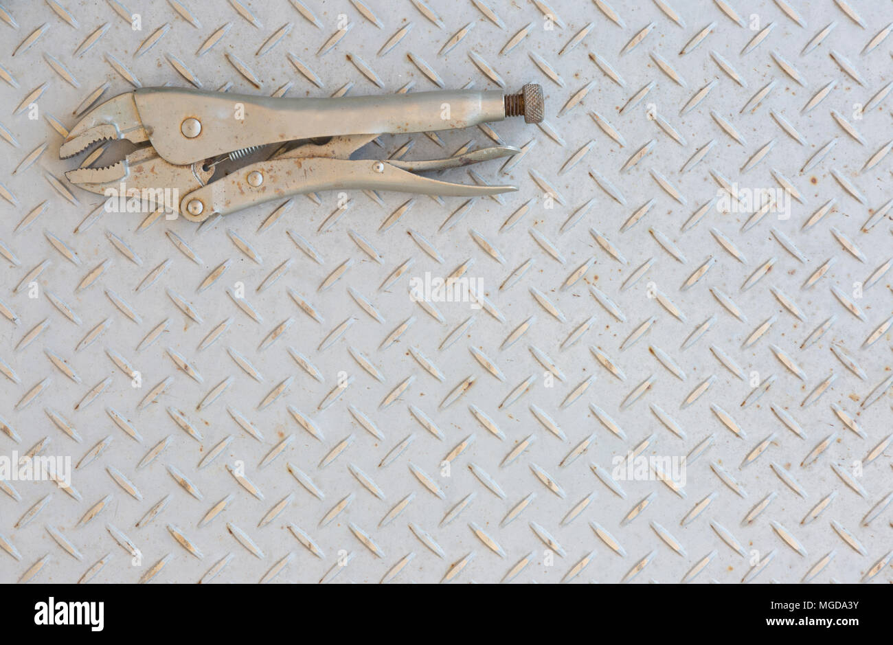 Vise grips or Vice grips on a checker plate floor. - Stock Image