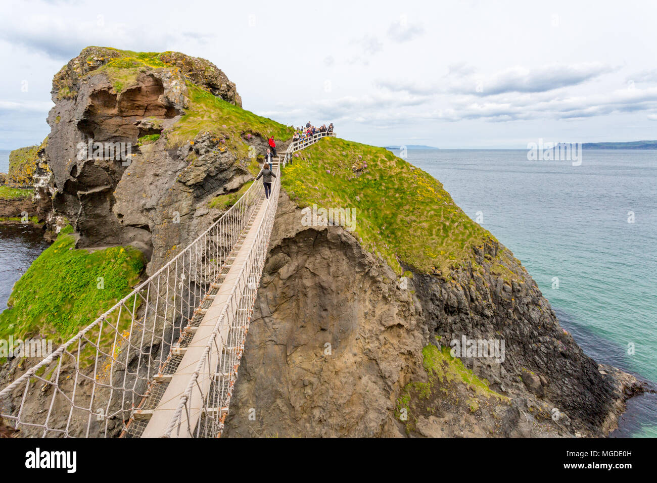 Antrim/N. Ireland - May 30, 2015: The scenic coast of N. Ireland and the Carrick-a-Rede Rope Bridge which connects the mainland with a small island. - Stock Image