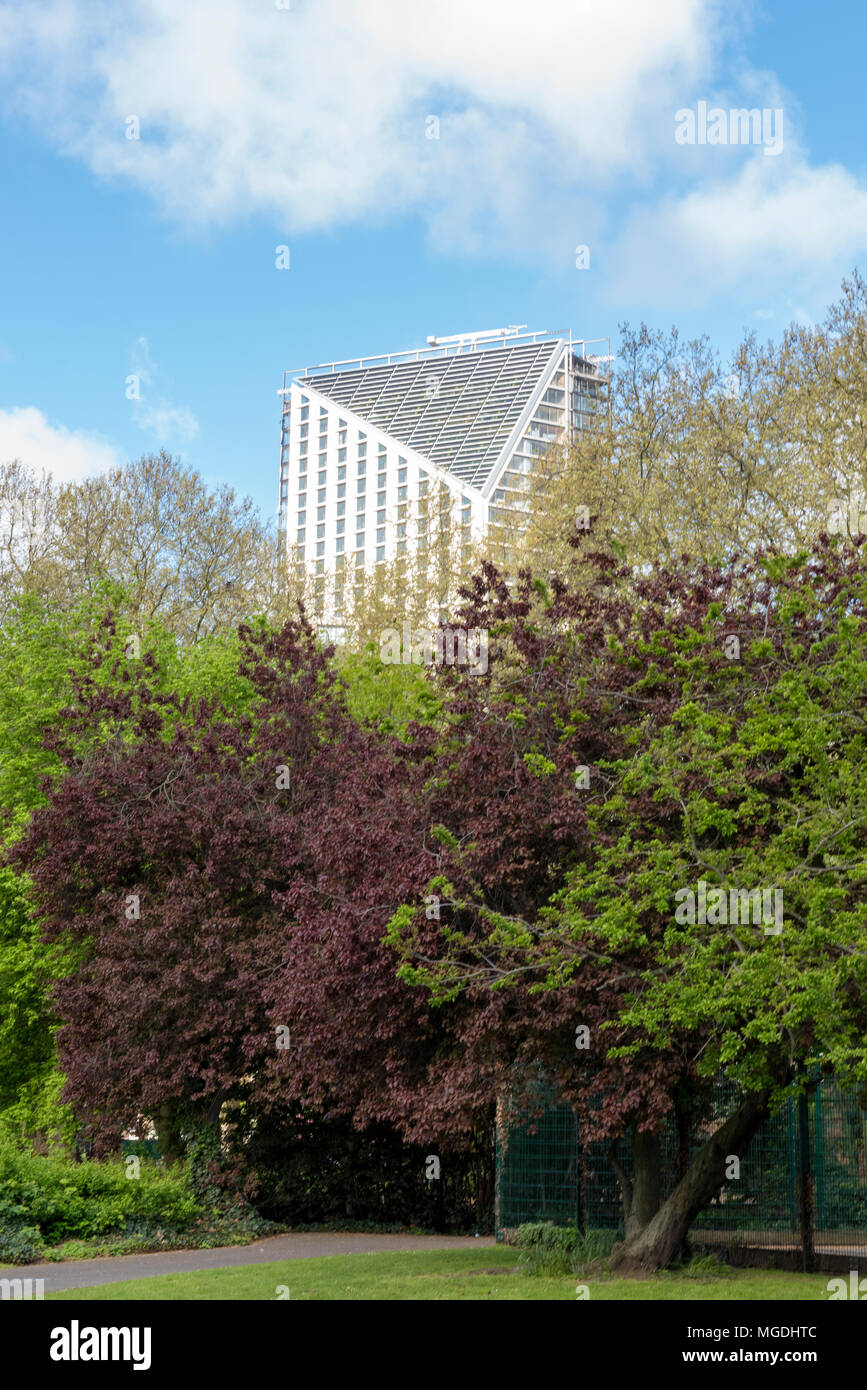 a modern or contemporary mult-storey block of flats or offices shows above the top of a green space in the centre of london. chalk and cheese. trees. - Stock Image