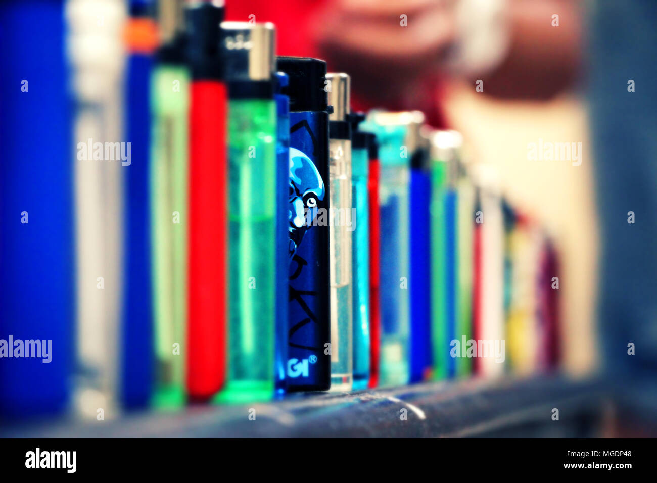 Lighters lined up. One lighter blue color stands out from the rest. Man's face Illustrated on it and it looks like he glances out. Narrow focus. - Stock Image