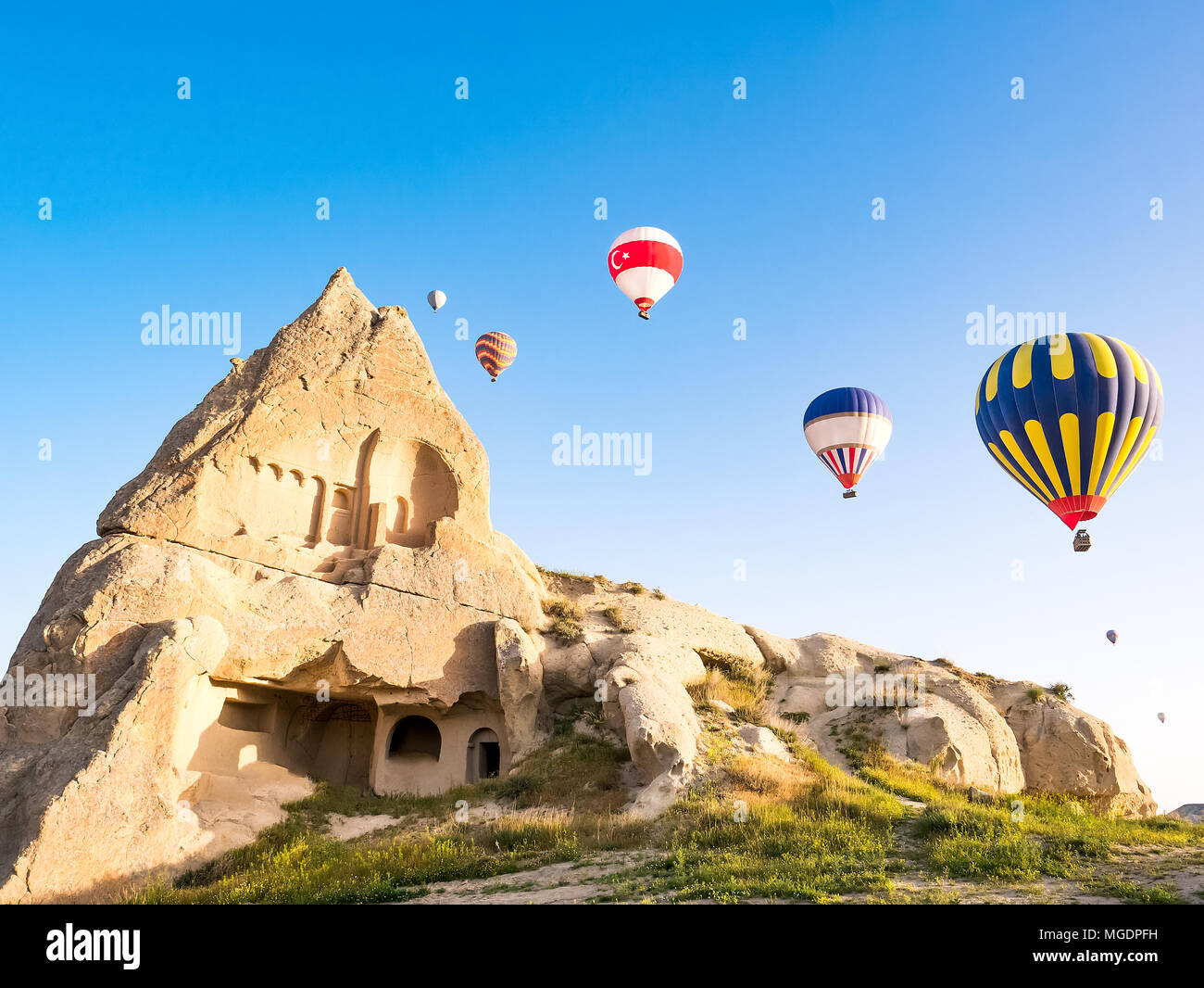 Colorful hot air balloons flying over rock landscape at Cappadocia Turkey Stock Photo