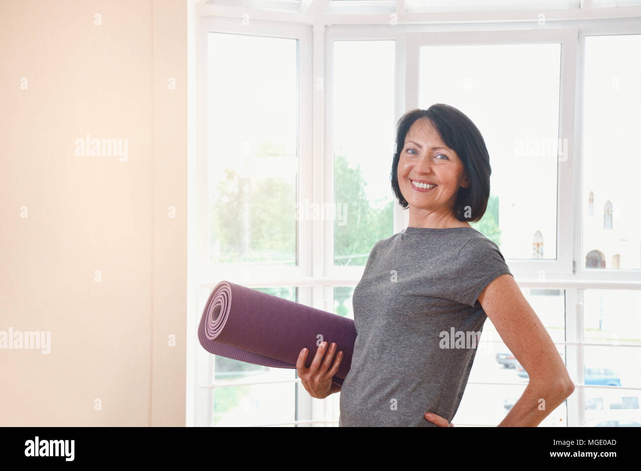 Mature woman holding rolled up exercise mat at gym. Cheerful female fitness instructor holding mat Stock Photo