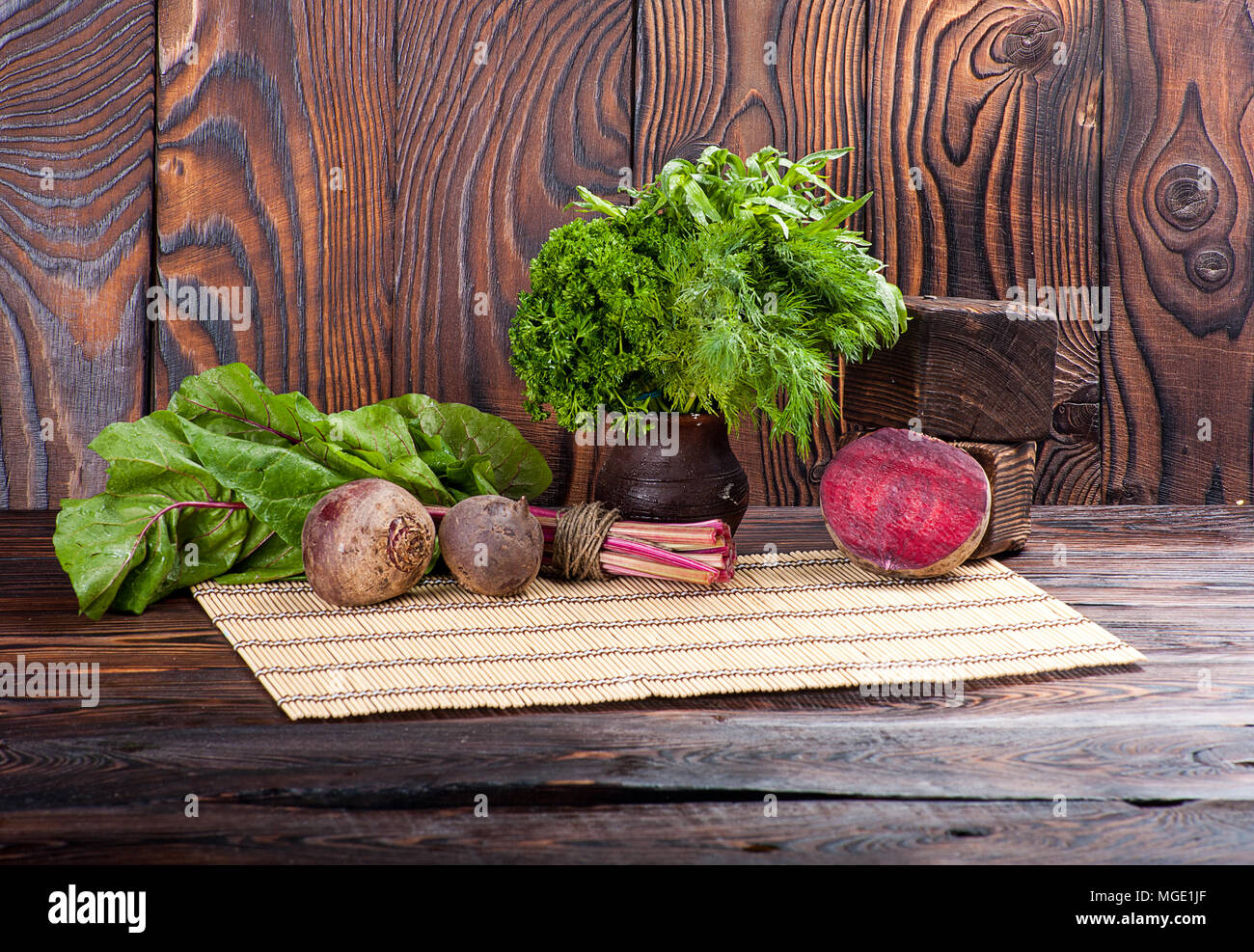 Still life of beetroot and beet leaves on wooden background - Stock Image
