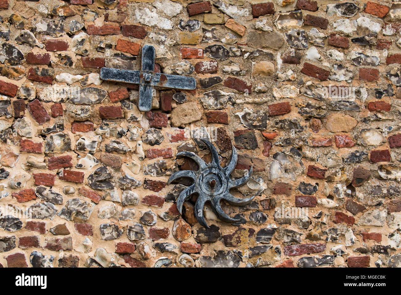 Anchor plates attached to old brick and flint wall. - Stock Image